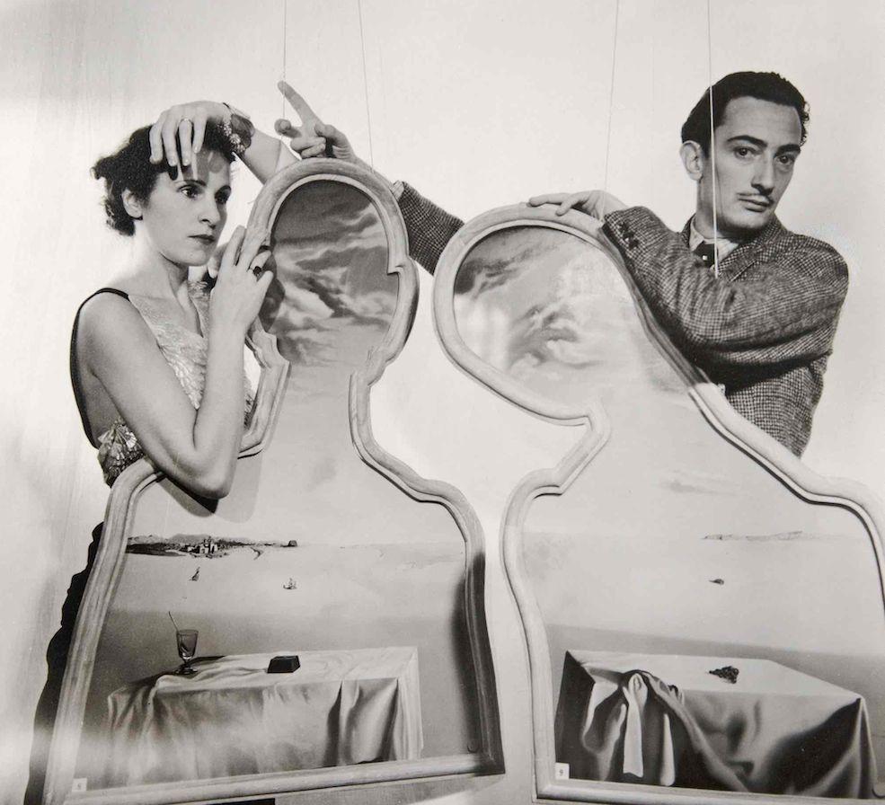Foto de Cecil Beaton de Gala i Dalí darrera de l'obra Parella amb els caps plens de núvols